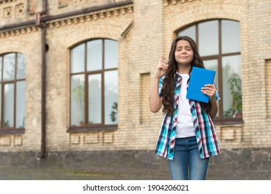 Ill keep my fingers crossed. Superstitious child make wish with closed eyes holding book. Following study superstition to pass exam. Playing ritual. School education. Superstition concept. Good luck.