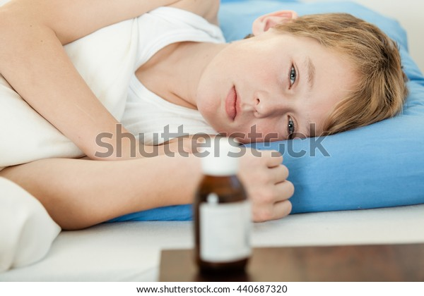 Ill male child in undershirt and weak expression laying down on blue pillow next to medicine bottle on table