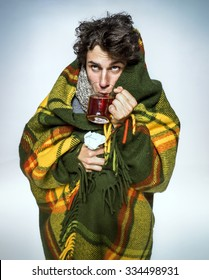 Ill Man covered with plaid blanket with hot tea/ sick man  suffering cold and winter flu virus. Medication or drugs abuse, healthcare concept
