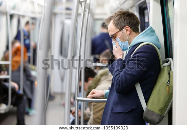 Ill man in glasses feeling sick, coughing, wearing protective mask against transmissible infectious diseases and as protection against the flu in public transport. New coronavirus 2019-nCoV from China