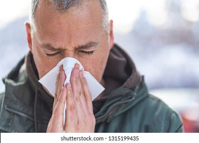 Ill man with paper tissue in winter nature - healthcare and medicine concept.  Man blowing his nose in bright snow forest. Man blowing his nose in the cold weather