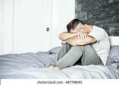 An Ill man sitting on his bed