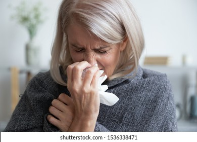 Ill mature woman covered with blanket blowing running nose sneeze in tissue suffer from allergy flu, allergic old lady hold handkerchief got hay fever rhinitis symptom cough at home, allergy concept