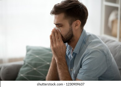 Ill millennial man sit on couch feel unwell blowing running nose with napkin, sick male at home have health problems, get flu or fever symptoms, tired guy suffer from sickness sneezing holding tissue