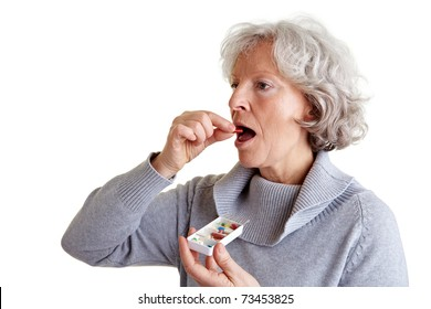 Ill old woman taking a pill from a pill dispenser