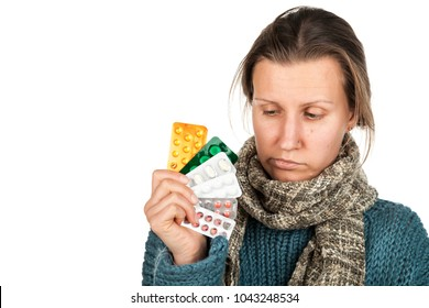 Ill person with symptoms of virus flu, headache, temperature and cough holds a stack of colorful medicine pills. Healthcare medical and pharmaceutical concept. Isolated on a abstract white background