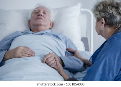 Ill, senior man lying in the hospital and his wife sitting beside him, holding his hand