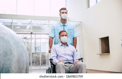 Ill senior man with protective safety mask on face in a wheelchair and a confident doctor in the medical mask while transporting on the hospital.