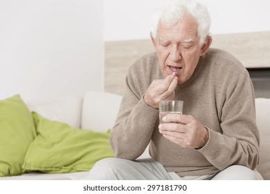 Ill senior man taking medicine for hypertension