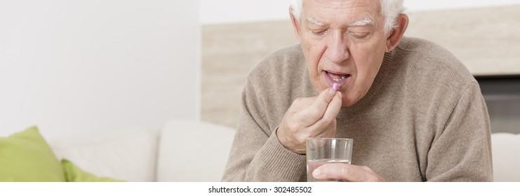 Ill senior man taking tablet for hypertension