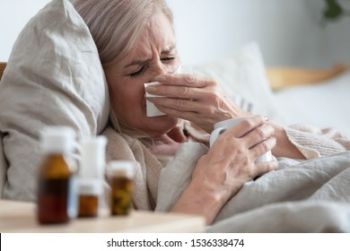 Ill sick middle aged woman sneezing blowing running nose holding tissue sit on bed, upset old mature lady caught cold got flu influenza grippe symptoms drink hot tea taking medications at home alone