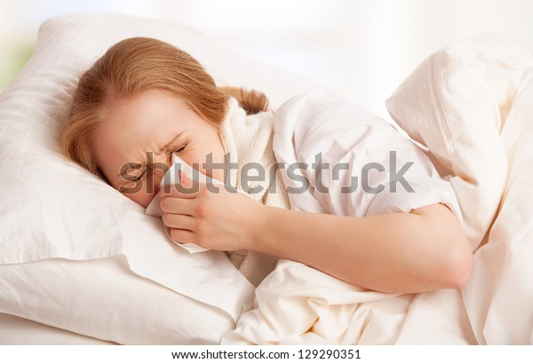 ill sick young woman sneezes and blows her nose into a handkerchief in bed