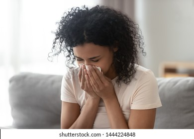 Ill upset african woman blowing running nose got flu caught cold sneezing in tissue sit on sofa, sick allergic black girl having allergy symptoms coughing holding napkin at home, hay fever concept
