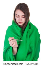 Ill woman covered with blanket holding  a thermometer in her hand