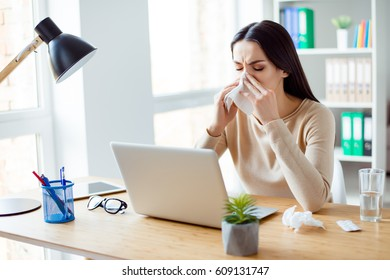 Ill woman sitting at the table with computer at work and using napkin.