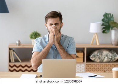 Ill at work young man got flu allergy sneezing blowing wiping running nose in tissue, allergic guy caught cold at job sitting at home office workplace having respiratory disease, sick leave concept
