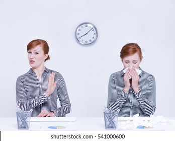Ill worker blowing nose and woman keeping distance from her