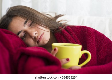 ill young girl with fever drinking cup of warm tea
