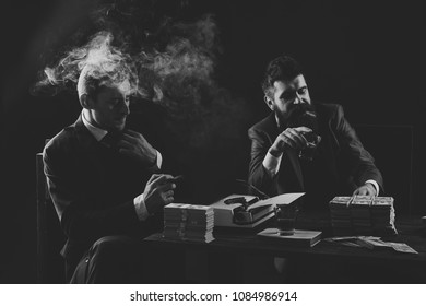 Illegal business concept. Businessmen discussing illegal deal while drinking and smoking, dark background. Company engaged in illegal business. Men sitting at table with piles of money and typewriter.