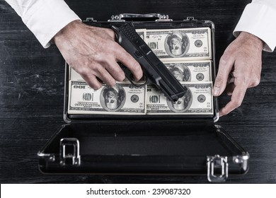 Illegal business. Top view of man holding gun and opening a briefcase full of paper currency