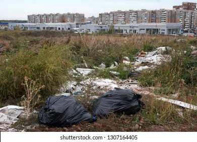Illegal city dump in the wasteland in the dry grass. Outskirts of a big city.