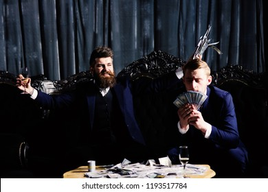 Illegal deal concept. Man holds cash, money, banknotes. Business partners counting money, profit of illegal business. Men in suit, businessmen sit in dark luxury interior background.