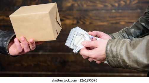 Illegal deal concept. Money cash in hand of criminal man. Crime and illegal profit. Break law. Dealer and buyer of illegal item. Buy illegal products. Cash money and box with forbidden goods exchange.