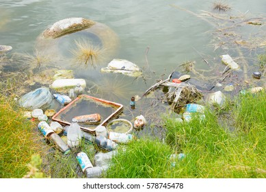 Illegal Dumped household garbage floating on water of lake, pond or river, contaminating, poisoning  environment.