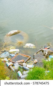Illegal Dumped household rubbish floating on water of lake, pond or river, contaminating, poisoning  environment.