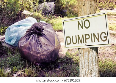 "Illegal dumping in the nature with ""No Dumping"" sign indicating in the countryside - concept image"