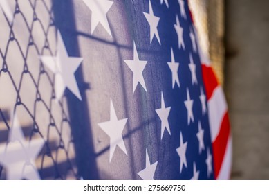 Illegal immigration concept  Background of transparent American flag behind a chain link fence and concrete stairway