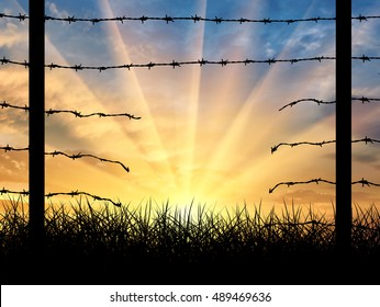 Illegal immigration. Silhouette of a broken border fence with barbed wire