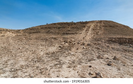 illegal off road track causing permanent damage in a protected nature reserve near the Makhtesh Ramon crater in Israel with a blue sky background