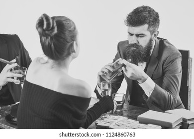 illegal transaction. Company engaged in illegal business. Men and woman sitting at table with piles of money. Illegal deal concept. Businessmen discussing illegal deal while drinking and smoking