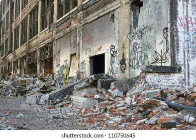 Illegally painted graffiti in an abandoned building in Detroit, Michigan. The Windows are broken out and piles of bricks and old tires are scattered about.