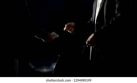 Illicit drug trafficking, man in suit paying for drug package near car, darkness