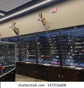 Illinois, USA; June 29, 2019: Long firearms for sale, displayed in the wall of a gun store in Elgin together with stuffed deer heads. Handguns, also for sale, are displayed in a glass showcase