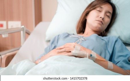 illness asia patient women and hospital concept - hand with iv solution of illness asian patient women on bed sleeping in patient room alone of hospital with flare light effect and copy space
