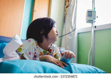 Illness asian child admitted in hospital while saline intravenous (IV) on hand. Unhappy girl depress and hopeless with absent minded looking outside, kid emotion. Health care stories.