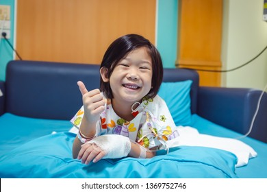 Illness asian child smiling happily and showing thumb up hand sign. Girl admitted in hospital while saline intravenous (IV) on hand. Health care stories.