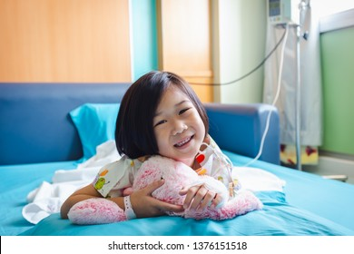 Illness asian child smiling happily and looking at camera. Girl admitted in hospital while saline intravenous (IV) on hand. Health care stories.