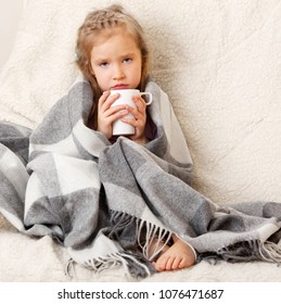 Illness child. Little girl wrapped in a blanket with mug