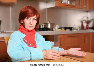 Illness grandmother holds pills and glass of water