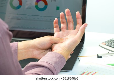 Illness hand. Portrait of a businessman with a beard while working in his office, holding hand