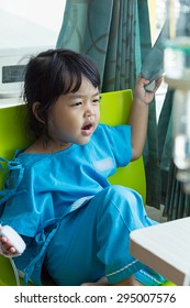 Illness little asian kids sit on a chair in hospital, saline intravenous (IV) on hand