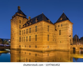 Illuminated 12th Century renovated Castle surrounded by water at twilight, Europe.