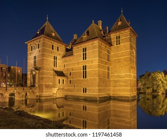 Illuminated 12th Century renovated Castle surrounded by water at night, Europe.