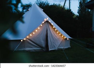 Illuminated bell tent at night, glamping