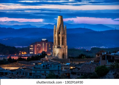 Illuminated bell tower of the Sant Feliu Basilica at dusk in city of Girona in Catalonia, Spain.