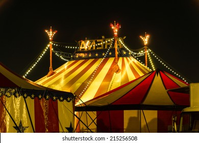 An illuminated big top at night with the nigh sky at background